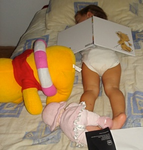 Avery and some of her favorite things: doll, Pooh and a book